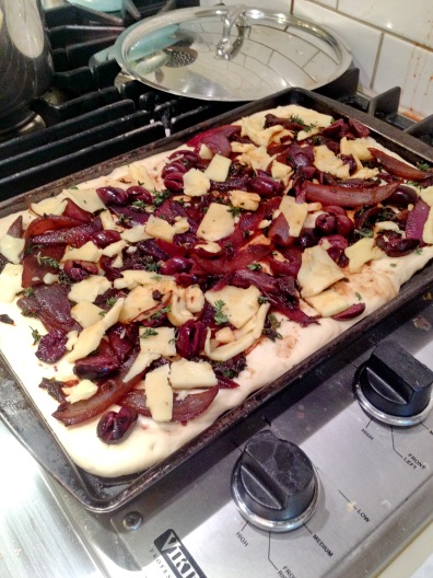 Flatbread with Kalamata olives waiting in line to oven